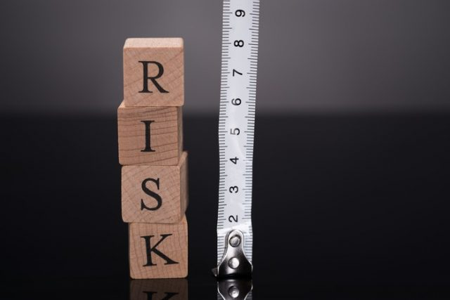 Measuring risks with ruler over black background