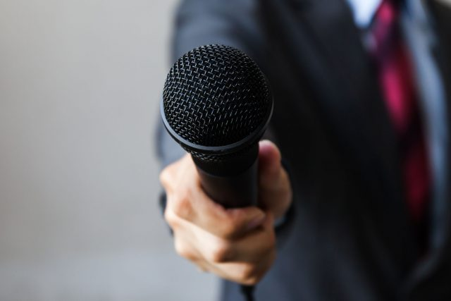 Ask an Expert: James A. Wollack - man in business suit holding a microphone conducting a business interview