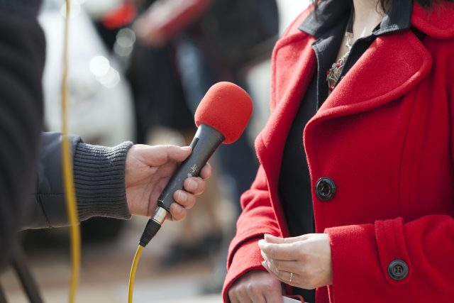 a journalist is conducting an interview with a microphone