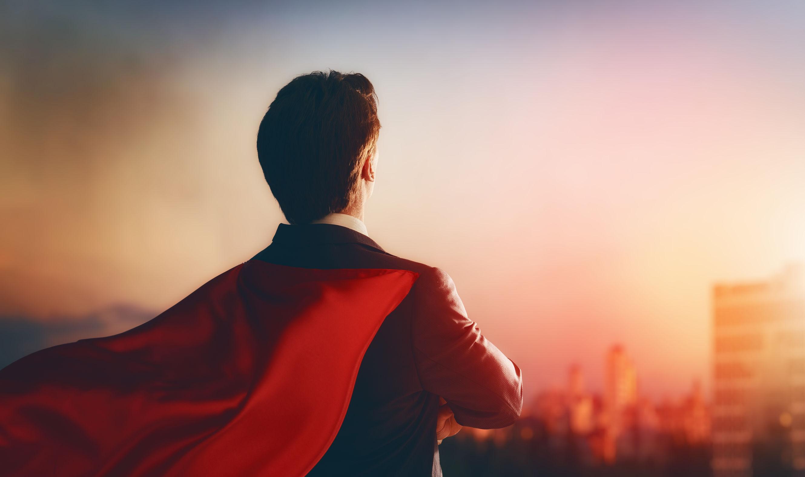 superhero businessman looking at city skyline at sunset.